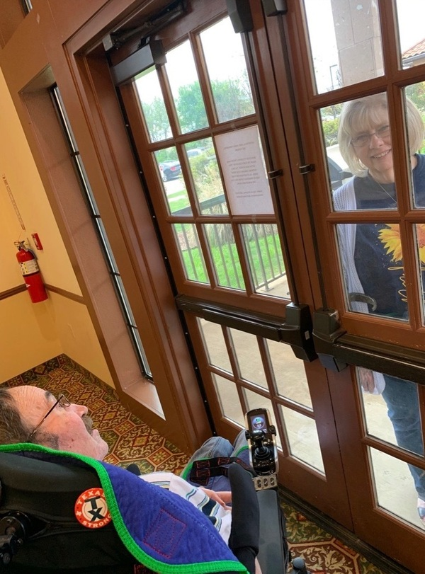 Luann visits Jeff at the nursing home, with a glass door between them.