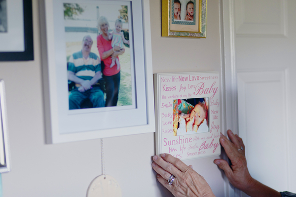 Luann adjusts a family photo at wall in her home. Before the coronavirus outbreak, she would take Jeff to church on Sunday and to the movies. They'd go out for fast food. But she says since the lock down, his anxiety has increased.