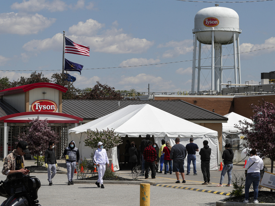 Workers line up to enter a Tyson Foods pork processing plant last month in Logansport, Ind. Some of the worst workplace coronavirus outbreaks have been in the meatpacking industry. Major meatpackers JBS USA, Smithfield Foods and Tyson have said worker safety is their highest priority. (Michael Conroy/AP)