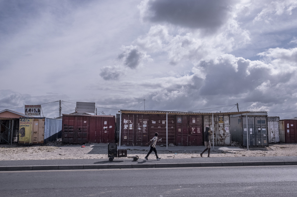 Boys walk past shuttered businesses in the township of Khayelitsha in Cape Town, South Africa, during the coronavirus lockdown. This recession is the first triggered solely by a pandemic, and low-income countries are particularly hard-hit. (Tommy Trenchard for NPR)