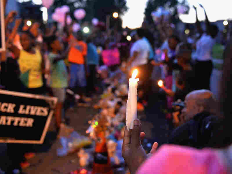 A girl holds a candle as children gather at the Michael Brown Jr. memorial on Canfield Drive during a candlelight vigil.