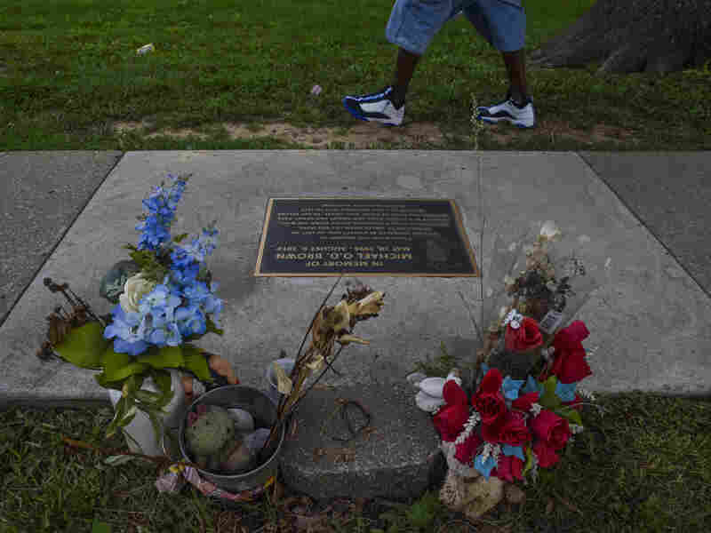FERGUSON, MO - : A plaque in memory of teenager Mike Brown is embedded in the sidewalk near the Canfield Apartments where Mike Brown killed.