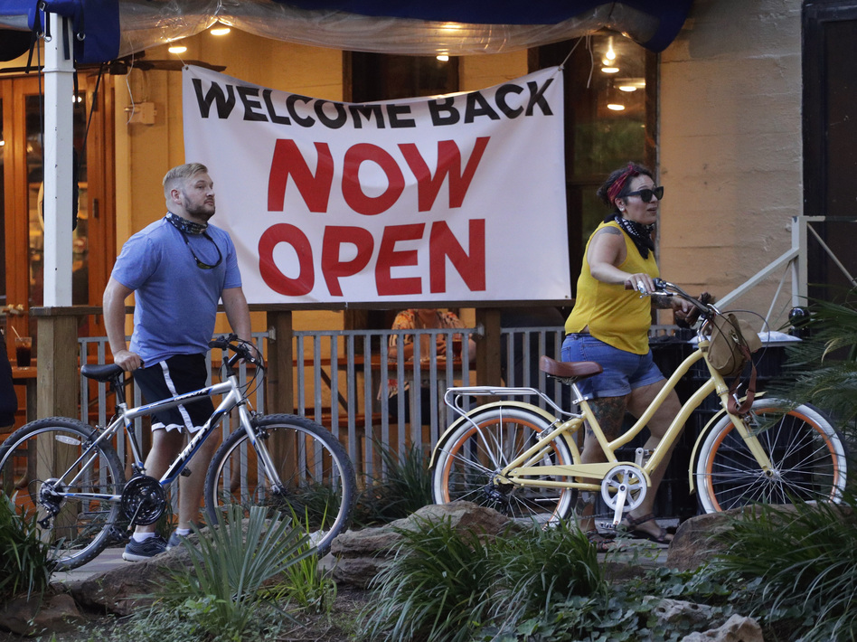 Visitors to the River Walk pass a restaurant that has reopened in San Antonio, Texas, on May 27. Texas continues to reopen in the wake of the COVID-19