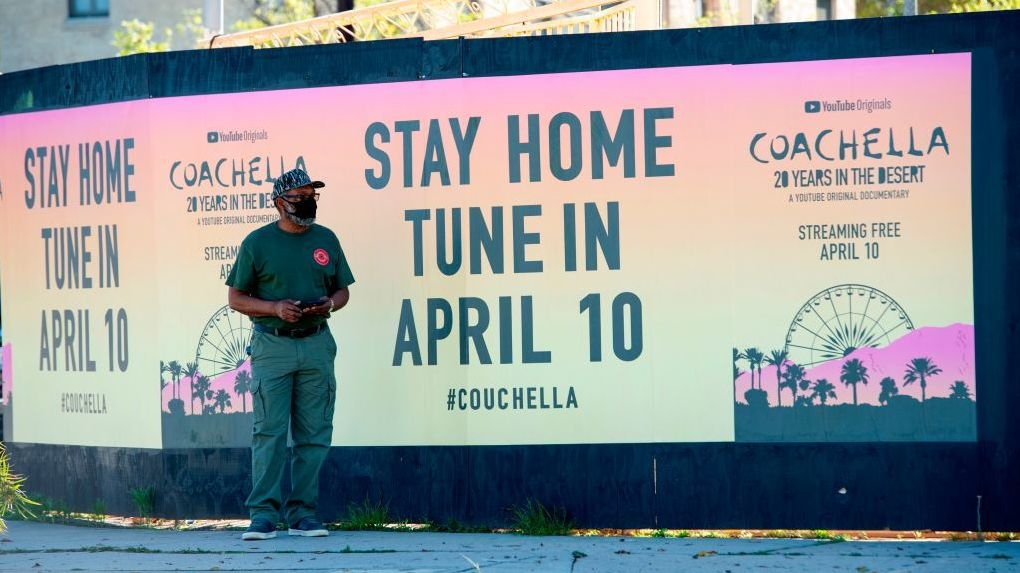 """A man stands in front a poster advertising an """"at home"""" streamed Coachella event in April in Hollywood, Calif."""