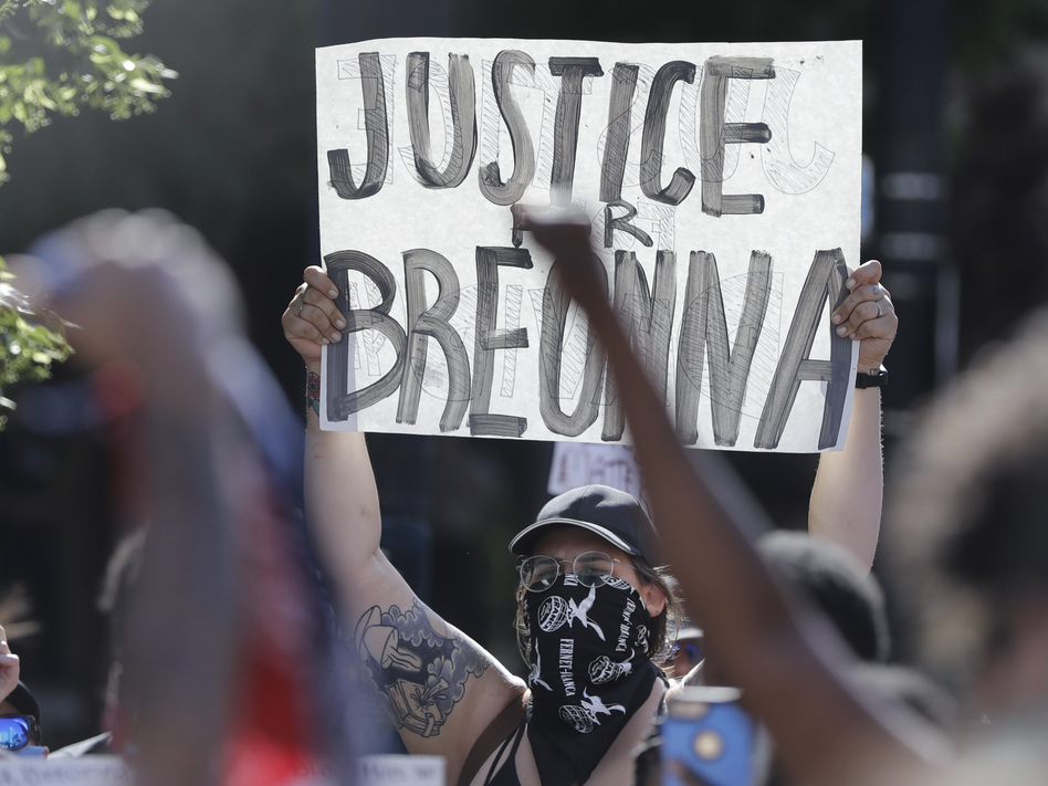 A protester holds a sign during a June 1 protest over the deaths of George Floyd in Minneapolis and Breonna Taylor in Louisville, Ky. (Darron Cummings/AP)