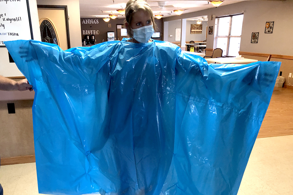 Kelly Womochil, an aide at Enterprise Estates Nursing Center in Enterprise, Kan., tries on a poncho that the Federal Emergency Management Agency is sending to nursing homes to protect against the coronavirus. (Pamela Black)