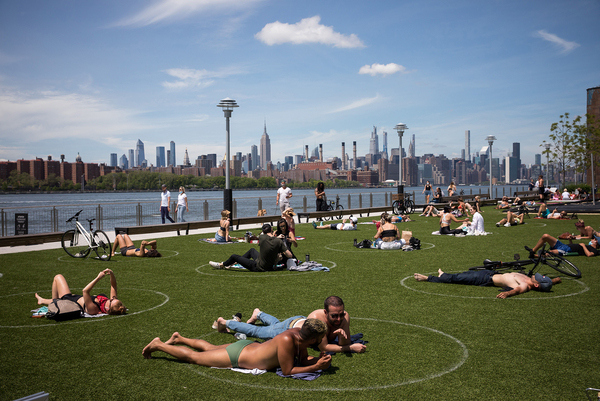 """People rest inside social distancing markers at Domino Park in the Brooklyn borough of New York in late May. Stay-at-home orders in New York helped to lower the state's """"reproduction number,"""" which estimates how many people one sick person could infect with the coronavirus."""