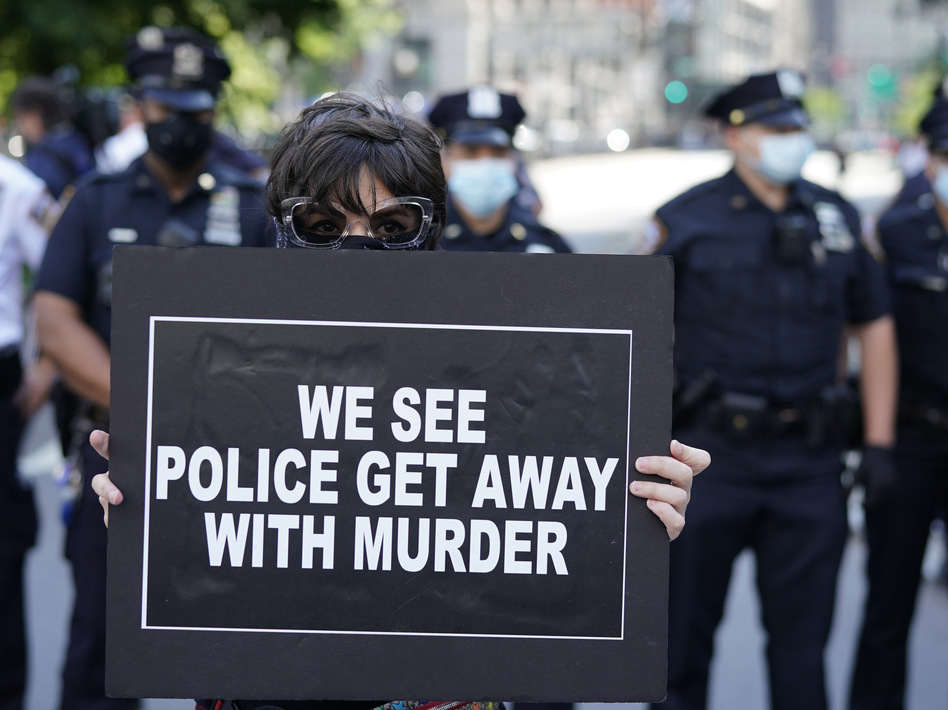 New York City Police officers stand behind a protester during a vigil at Foley Square in New York last month. (Timothy A. Clary/AFP via Getty Images)