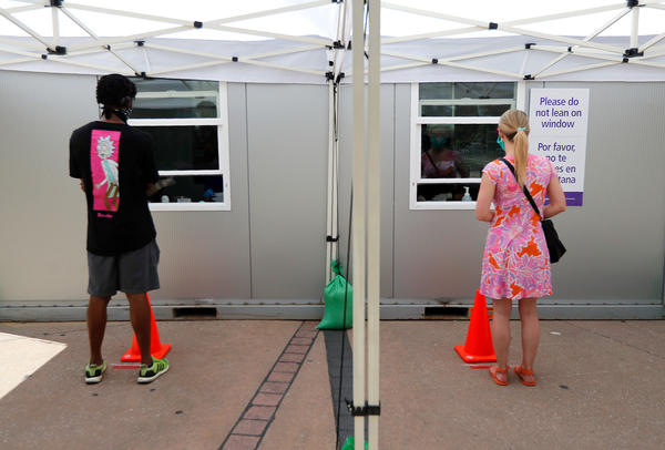 Parkland Memorial Hospital employees give instructions to a man and a woman on how to self-administer a test for the coronavirus at a Dallas walk-up facility. Texas saw a surge in cases within the past week.