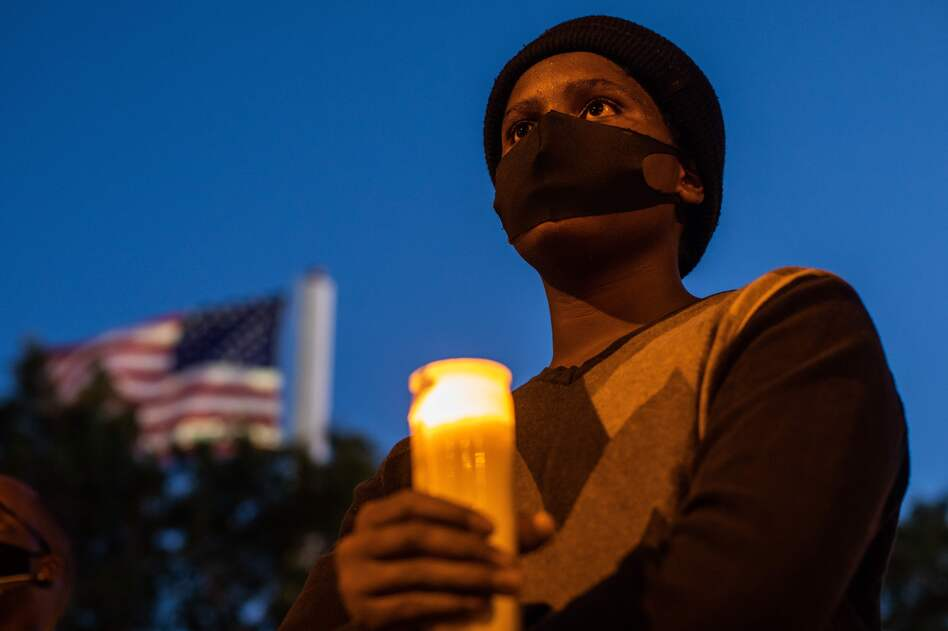 A man holds a candle during a vigil around a makeshift memorial at the tree where Robert Fuller was found dead hanging from a rope in Palmdale, Calif. Officials deemed Fuller's death a suicide, but his family wants an independent investigation. (Apu Gomes/AFP via Getty Images)