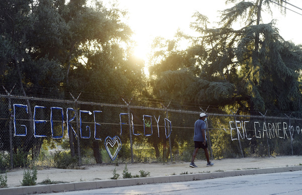 A walker passes the names of George Floyd and Eric Garner spelled out in fabric at the Say Their Names: Silver Lake Memorial on June 9 in Los Angeles. There has been a recent push for a nationwide ban on police chokeholds.