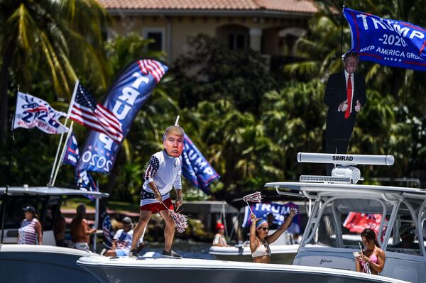 A supporter of President Trump wears a mask and dances during a boat rally to celebrate Trump's birthday in Fort Lauderdale, Fla., on Sunday.