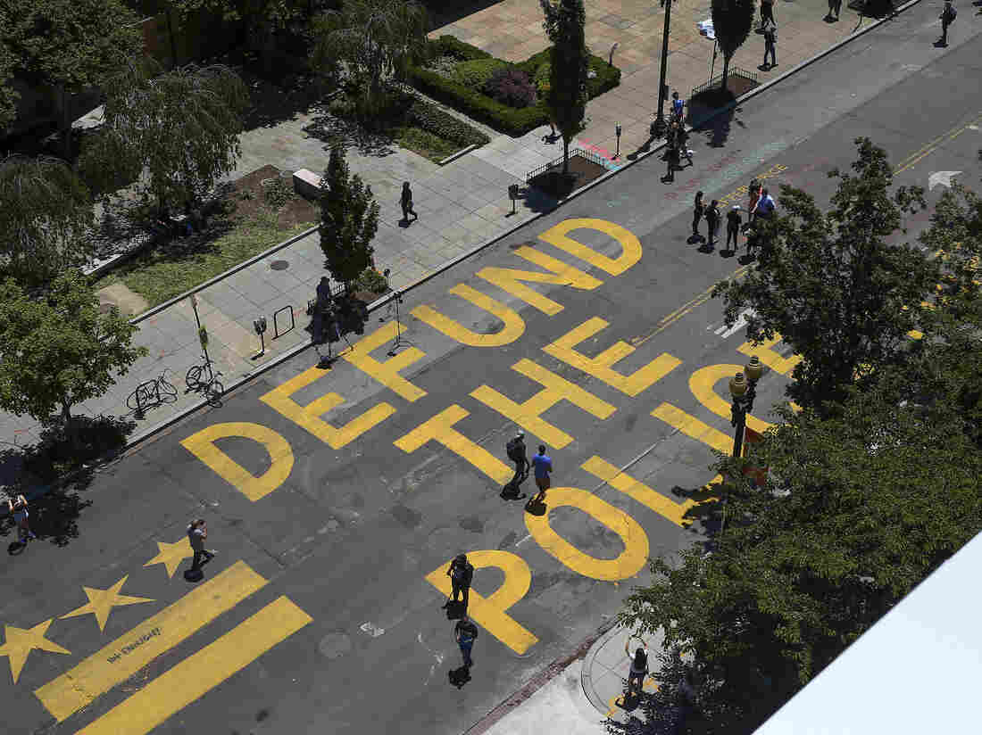 "People walk down 16th street after ""Defund The Police"" was painted on the street near the White House on June 08, 2020 in Washington, DC. (Photo by Tasos Katopodis/Getty Images)"