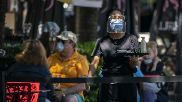 A server wears a protective face mask while attending to customers amid the COVID-19 pandemic in Bethesda, Md., on June 12.