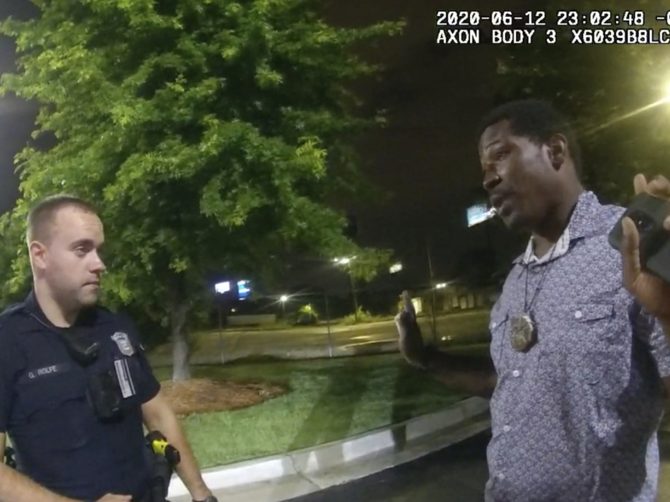 This screen grab taken from body camera video provided by the Atlanta Police Department shows Rayshard Brooks speaking with Officer Garrett Rolfe in the parking lot of a Wendy's restaurant on June 12 in Atlanta. Rolfe has been fired following the fatal shooting of Brooks, and a second officer has been placed on administrative duty. (Atlanta Police Department via AP)