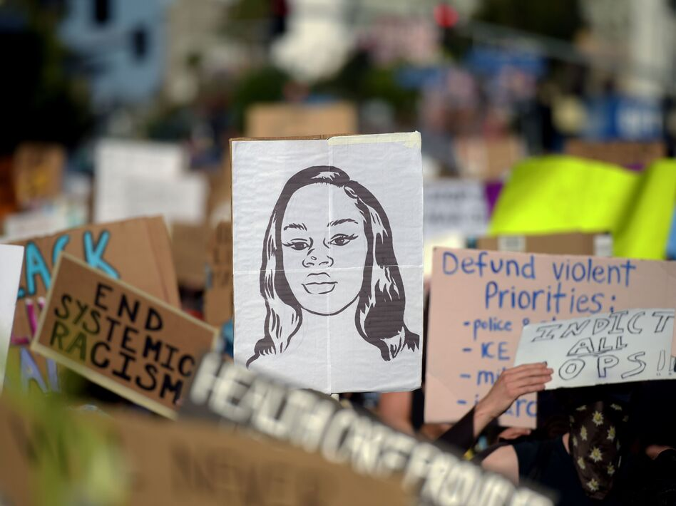 Protesters march with placards and a portrait of Breonna Taylor during a demonstration against racism and police brutality this month in Hollywood, Calif. The mayor of Louisville, Ky., has announced that an officer involved in her death will be fired. (Agustin Paullier /AFP via Getty Images)