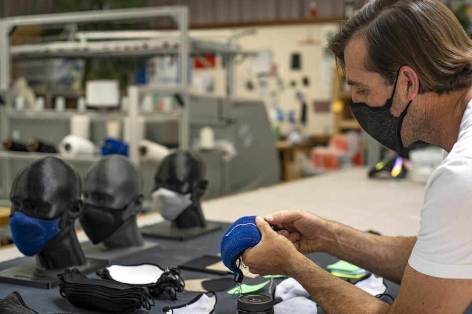Billy Smith counts rows in the knit structure of a mask to ensure that specifications for fit and sizing meet company standards. (Nick Rubalcava/Bilio)