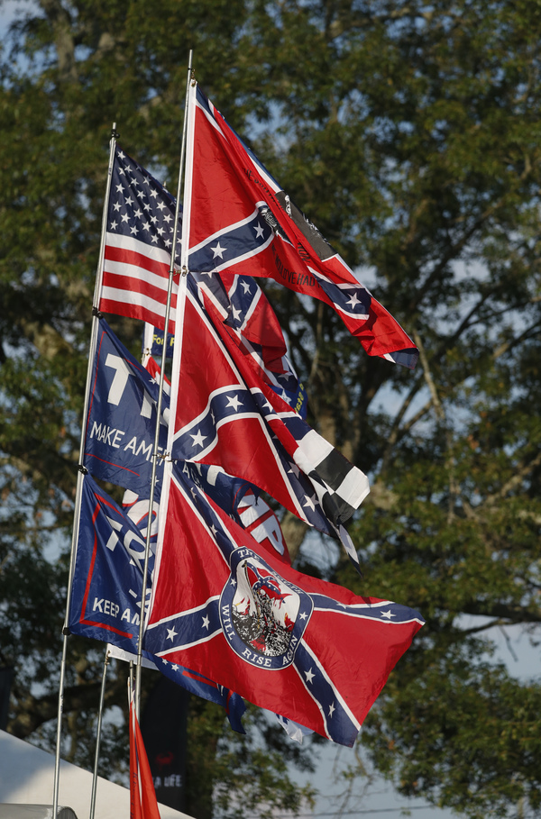 A vendor displays Confederate flags as well as Trump 2020 flags across from the Talladega Superspeedway in Talladega, Ala., on Saturday. NASCAR has banned the Confederate flag from its facilities and events.