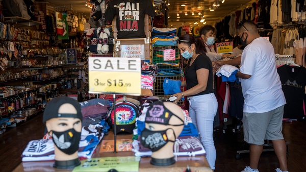 People wearing protective masks shop for clothing at a store on Fishermans Wharf in San Francisco on Monday.