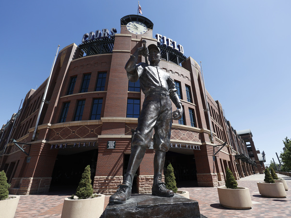 A bronze baseball player stands outside Coors Field in Denver, one of the stadiums idled during the coronavirus outbreak. The league and players association have agreed to  league is waiting for the players' union to respond to whether it will agree to play a shortened season beginning in late July.