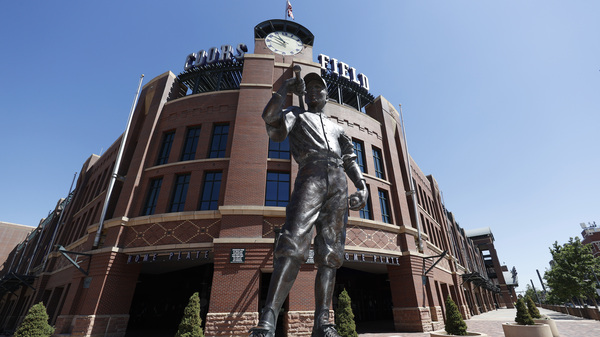A bronze baseball player stands outside Coors Field in Denver, one of the stadiums idled during the coronavirus outbreak. The league and players association have agreed to  league is waiting for the players