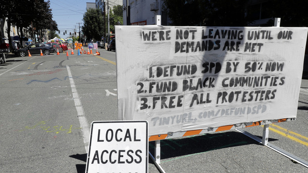 """The Seattle Police Department will return to their East Precinct building """"in the near future,"""" Mayor Jenny Durkan says. Here, a sign on a street barricade lists protesters"""