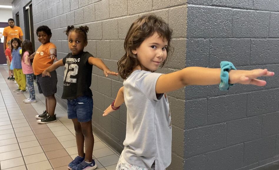 """To help with social distancing, children at Valley of the Sun YMCA sites in Arizona were taught to make """"airplane arms"""" when standing in line. (Valley of the Sun YMCA)"""