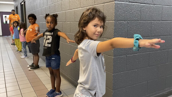 """To help with social distancing, children at Valley of the Sun YMCA sites in Arizona were taught to make """"airplane arms"""" when standing in line."""