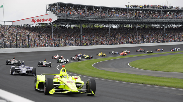 The Indianapolis 500 — usually viewed by hundreds of thousands of spectators — will be run in August in front of a crowd capped at 50% capacity, track officials say. Here, cars race in front of fans during last year