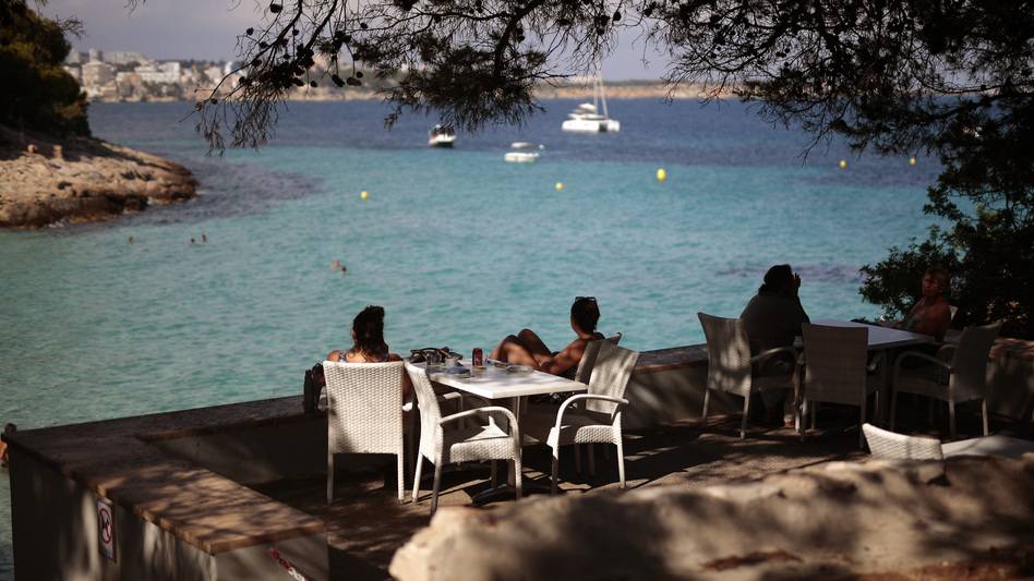 People sit in a terrace bar at the beach in Spain earlier this month, when many internal travel restrictions were lifted. The EU has decided on its first list of approved travel partners, as part of its reopening of external borders. (Joan Mateu/AP)