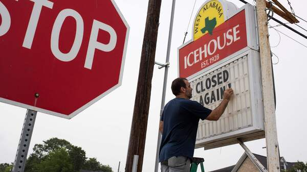 """Bar owner Petros J Markantonis changes the marquee outside his bar to """"Closed Again"""" at the West Alabama Ice House in Houston."""