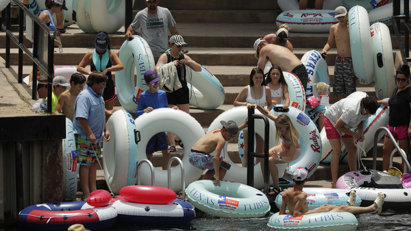 "Tubers prepare to float the Comal River in New Braunfels, Texas, on Thursday, despite the recent spike in COVID-19 cases. Texas Gov. Greg Abbott said Wednesday that the state is facing a ""massive outbreak"" of the coronavirus and that some new local restrictions may be needed to preserve hospital space for new patients."