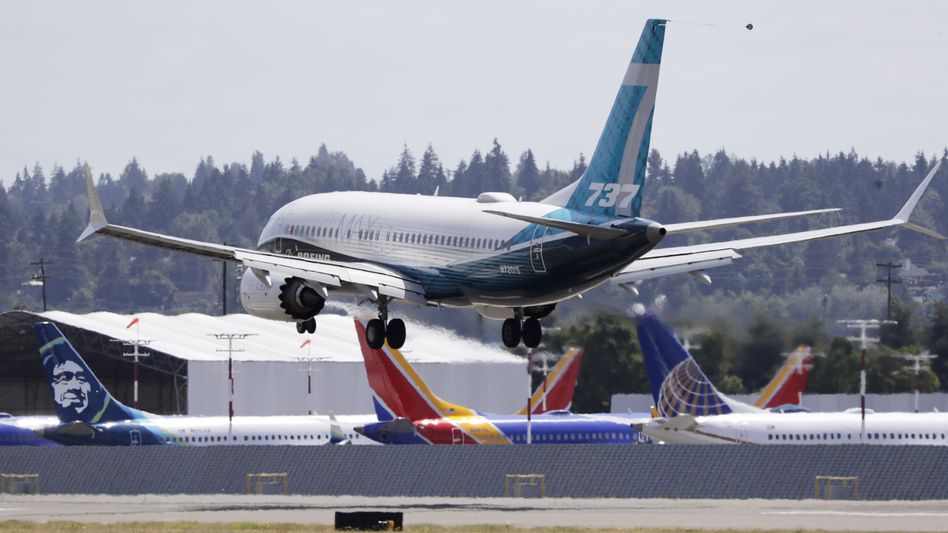 A Boeing 737 Max heads to a landing past grounded 737 Max aircraft at Boeing Field following a test flight Monday in Seattle. The jet took off from Boeing Field earlier in the day, the start of three days of re-certification test flights that mark a step toward returning the aircraft to passenger service. (Elaine Thompson/AP)