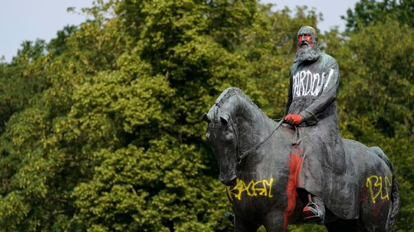 """A statue of King Leopold II stands defaced after protests earlier this month in Brussels. Belgian King Philippe sent his """"regrets"""" over the violent colonial policies kick-started by his predecessor."""