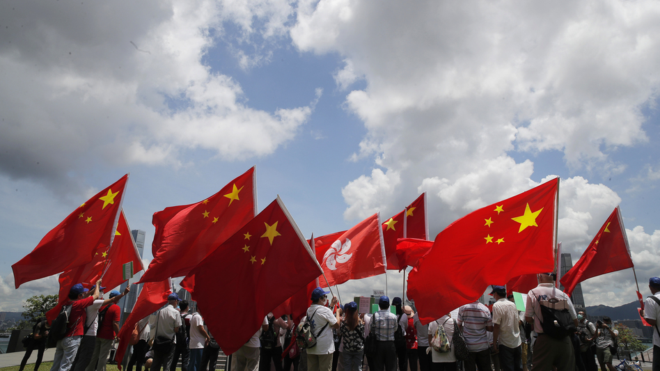 Pro-mainland supporters in Hong Kong hold Chinese and Hong Kong flags during a rally to celebrate the approval of a national security law on Tuesday. (Kin Cheung/AP)