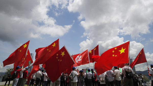 Pro-mainland supporters in Hong Kong hold Chinese and Hong Kong flags during a rally to celebrate the approval of a national security law on Tuesday.