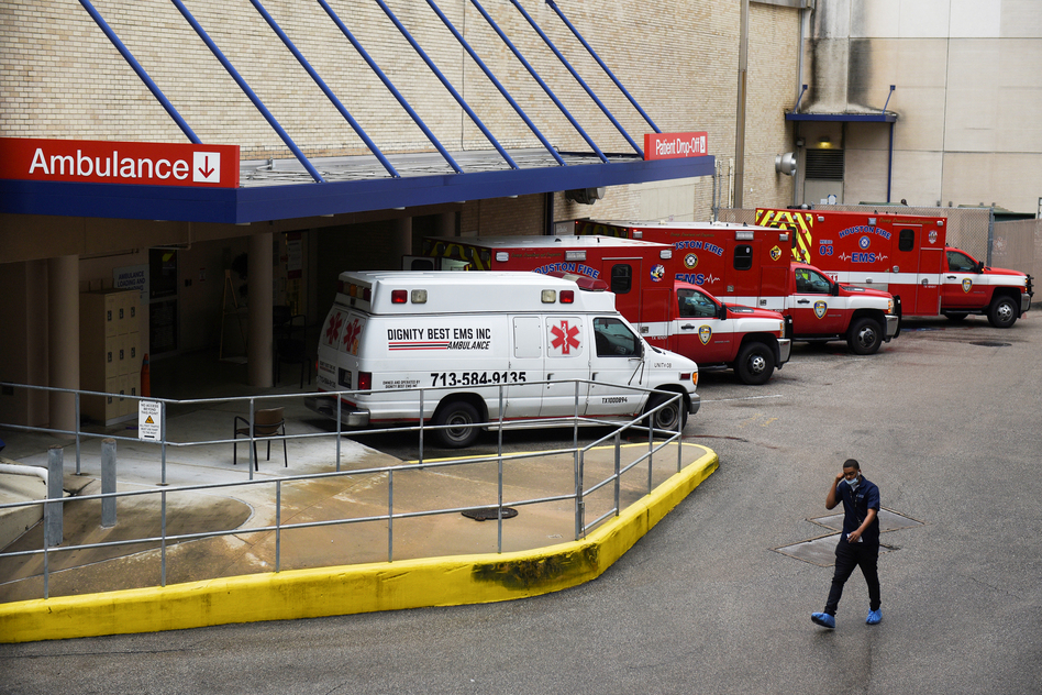 A medical worker walks past a row of ambulances parked outside Houston Methodist Hospital on June 22. The hospital is treating a current surge of COVID-19 cases. (Callaghan O'Hare/Reuters)