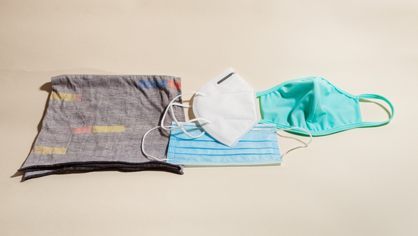 Left to right: neck gaiter (aka a buff) that slips over the head; the KN95, a version of the N95 used in U.S. hospitals; pleated surgical mask (below the KN95); cloth mask.