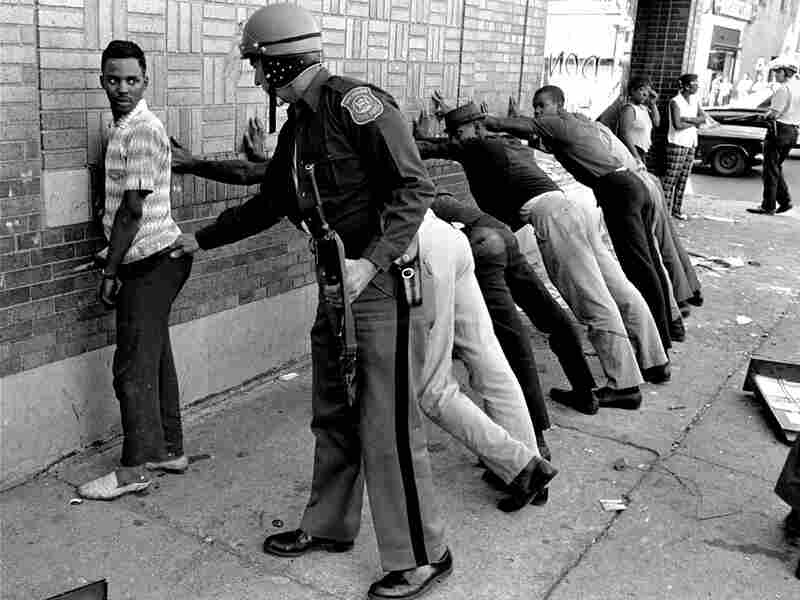 A Michigan state officer searches someone on Detroit's 12th Street where looting was still in process, July 24, 1967. Others lean against the wall waiting to be searched.
