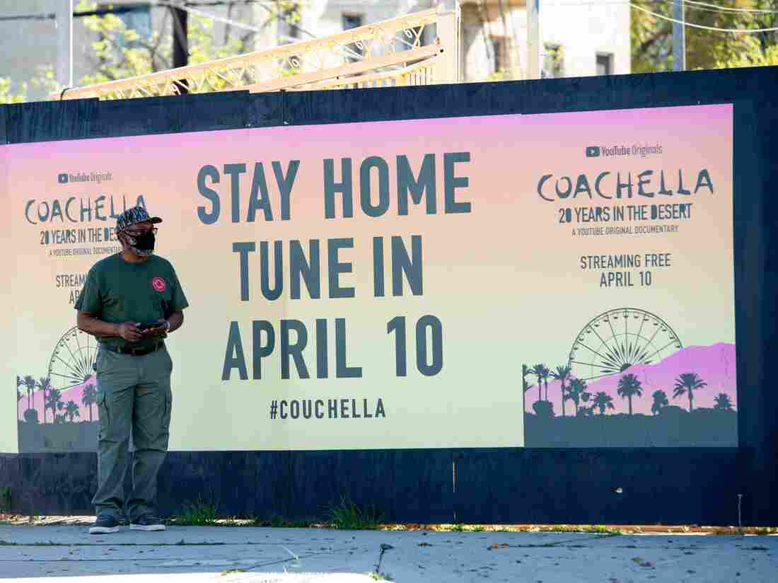 A man wearing a mask stands in front of a poster of Coachella on La Brea Avenue during the COVID-19 crisis. (Photo by VALERIE MACON/AFP via Getty Images)