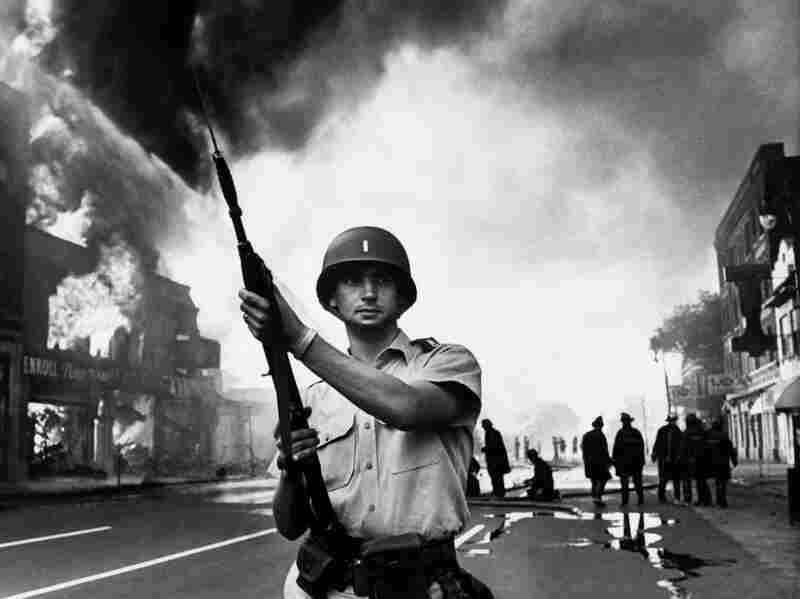 A Michigan State officer stands on guard on as buildings burn in Detroit, July 25, 1967.