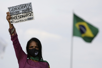 """A women's movement activist holds a sign that reads in Portuguese """"Genocide 60 thousand deaths, Bolsonaro out,"""" during a protest against the government's handling of the pandemic earlier this month."""