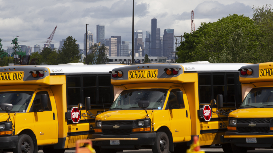 School buses sit idle in a Seattle bus yard. On July 2, Seattle Public Schools announced it is planning to resume some in-person learning in the new school year. (Karen Ducey/Getty Images)
