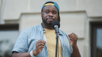 """""""People started screaming and shouting for them to let me go,"""" says Vauhxx Booker, who says he was assaulted by a group of white men on July 4. Booker is seen here speaking at a community gathering against racism, where protesters demanded charges in his case."""