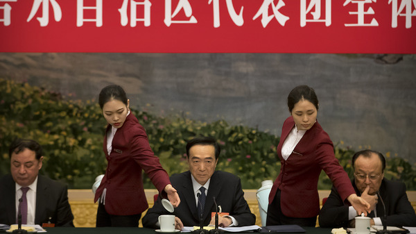 Attendants refill teacups as Chen Quanguo (center), Communist Party secretary of China