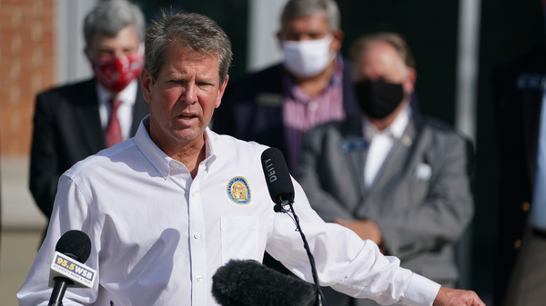 Georgia Gov. Brian Kemp holds a protective mask while speaking during a