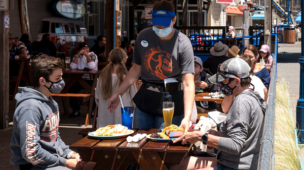 Patrons wear masks as they sit on the outdoor patio of a restaurant on Pier 39 at Fisherman