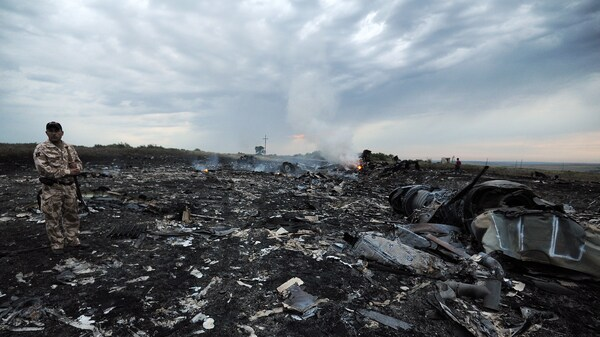A man wearing military fatigues stands next to the wreckage of Malaysia Airlines MH17 carrying 298 passengers and crew, that crashed in eastern Ukraine six years ago.
