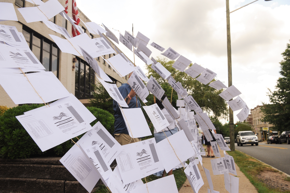 A rally outside the Montclair, N.J., town hall on July 1. Protesters hung 1,101 absentee ballots to represent the number of votes that weren't counted in a mayoral election that was decided by just 195 votes. (Kate Albright/Montclair Local)