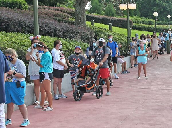 Guests wearing protective masks wait to pick up their tickets at the Magic Kingdom park. Reservations are required as well as masks and temperature checks prior to entering the park.